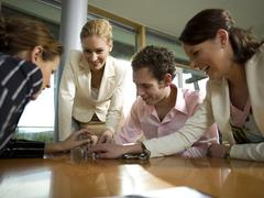 Business people assembling magnetic balls Stock Photos