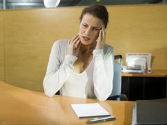 young woman sitting at desk having head ache - stock photo