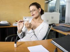 Woman in office, applying nail polish Stock Photos