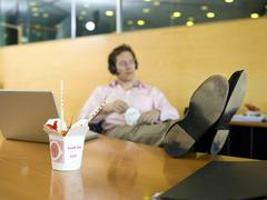 young man in office having lunch break - stock photo