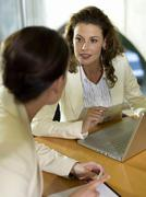 businesswomen sitting at desk with laptop - stock photo