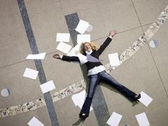 Woman lying on floor surrounded by papers, elevated view Stock Photos
