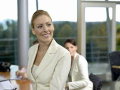 Young female professional in office, smiling Stock Photos