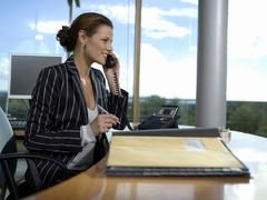 businesswoman working in office, using landline phone - stock photo