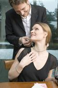 man fastening necklace on woman's neck - stock photo