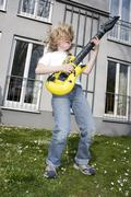 Stock Photo of boy 10-11) playing on toy guitar