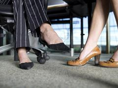 Women´s legs under desk Stock Photos