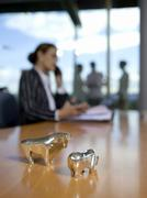 Figurines of bull and bear on desk (focus on foreground) Stock Photos