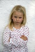 Girl (7-8) standing with arms crossed, frowning, portrait - stock photo