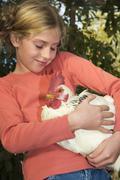 girl holding cock, portrait - stock photo
