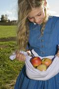 Stock Photo of girl (7-9) carrying apples in apron, close-up