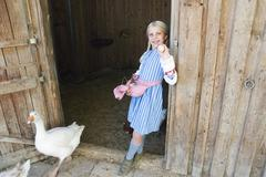 girl carrying eggs in apron - stock photo
