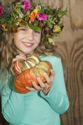 Girl (7-9) wearing wreath of flowers, holding pumpkin, portrait, close-up Stock Photos