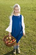 Stock Photo of girl holding basket with apples