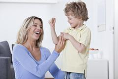 Son showing muscle to his mother Stock Photos