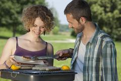 Stock Photo of Germany, Munich, Man serving sausage in plate, woman smiling