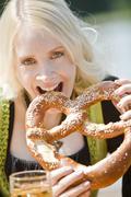 Stock Photo of Germany, Bavaria, Munich, English Garden, Young woman eating soft pretzel,