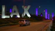 Stock Video Footage of Cars pass by the LAX sign on their way into Los Angeles airport.