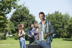 Germany, Munich, Man cooking food and friends in background - stock photo