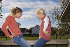 Two girls (8-11) on wooden railing, hand on hip, side view Stock Photos