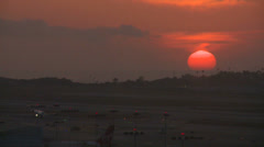 An orange ball of sun sets behind the LA hills. Stock Footage
