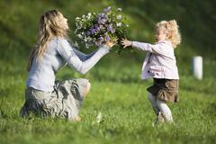 daughter giving mother bunch of flowers, side view - stock photo
