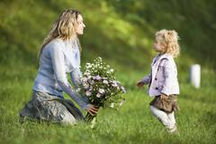 Mother and daughter wirth bunch of flowers, side view Stock Photos