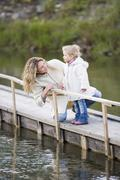 mother with daughter on jetty - stock photo