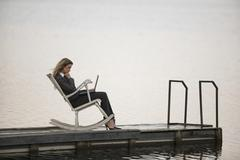 Businesswoman sitting in rocking chair on jetty, using laptop, side view Stock Photos
