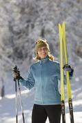 Austria,Tyrol, Seefeld, Wildmoosalm, Woman holding cross-country skis - stock photo