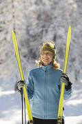 Stock Photo of Austria,Tyrol, Seefeld, Wildmoosalm, Woman holding cross-country skis