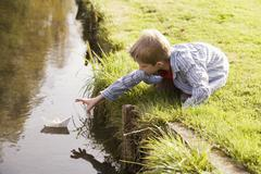 Stock Photo of boy (10-12) putting paper boat in river