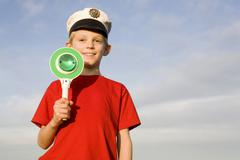 Boy (10-13) wearing police cap Stock Photos
