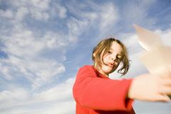 girl (7-9) holding paper plane, blurred motion - stock photo