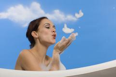 Young woman in bubble bath, blowing suds from hands, side view Stock Photos