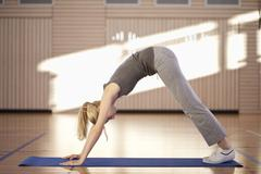 Germany, Mauern, Woman bending and exercising on exercise mat, looking down - stock photo