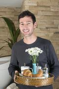 Stock Photo of Young man carrying tray with breakfast, smiling, portrait