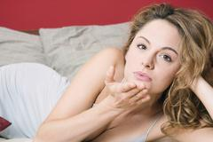 Stock Photo of Young woman on bed blowing a kiss, portrait