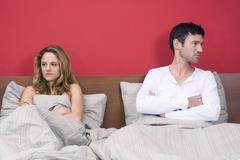 Young couple ignoring each other in bed, portrait - stock photo