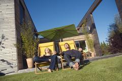 Stock Photo of Germany, Bavaria, Munich, couple sunbathing on loungers