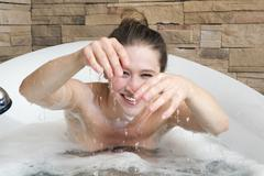 Young woman in bathtub fooling about Stock Photos