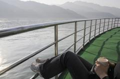 Stock Photo of China, Yangtze river, Person relaxing on board ship, low section