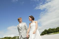 Germany, Bavaria, Bride and groom walking in park, holding hands, smiling, Stock Photos