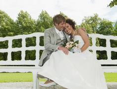 Germany, Bavaria, Wedding couple on bench, outdoors, smiling, portrait Stock Photos