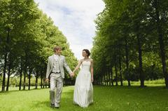 Stock Photo of Germany, Bavaria, Bridal couple in park walking hand in hand, smiling, portrait