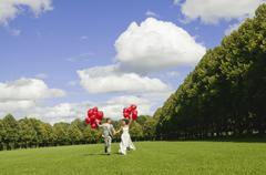Germany, Bavaria, Bride and groom holding red balloons, outdoors - stock photo