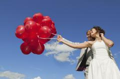 Germany, Bavaria, Bride and groom holding balloons, outdoors, portrait, low Stock Photos