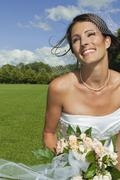 Stock Photo of Germany, Bavaria, Bride in park holding bunch of flowers, portrait, close-up