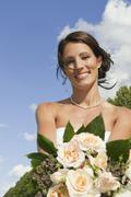 Germany, Bavaria, Bride holding bunch of flowers, portrait, close-up - stock photo