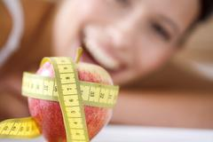 Stock Photo of Measuring tape wrapped round apple, woman in background